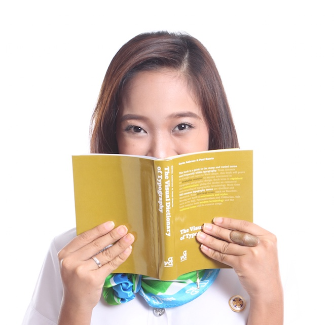 Student hiding her face with a book